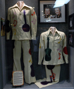A photograph of the exhibit containing the Wilburn Brothers Nudie suits with guitar and banjo on display at the Willie Nelson and Friends Museum.