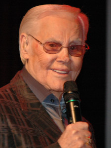 Photograph of George Jones singing at the Ryman Auditorium in Nashville, TN.