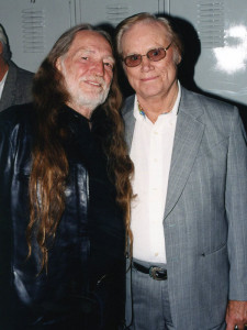 Photograph of George Jones and Willie Nelson taking a break while chatting backstage at the Grand Ole Opry in Nashville, TN.