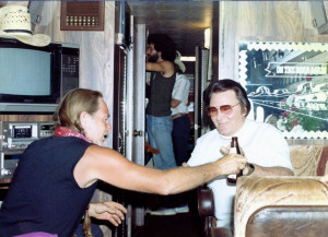 A candied photograph of Webb Pierce and Willie Nelson sharing a cold beer on Willie's bus named the Honeysuckle Rose during a stop in Nashville.