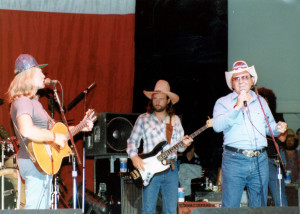 "A photograph of Webb Pierce joining Willie Nelson and band on stage during the premier of the ""Outlaw Channel"" television network that originally aired from the Willie Nelson Museum in Nashville, TN."