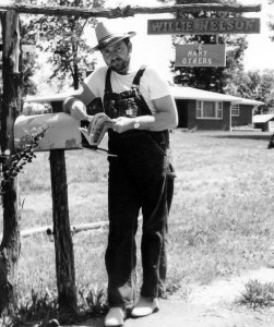 A photograph of Willie Nelson in overalls at the mailbox of his home in Ridgetop, TN in the 1960s when Willie Nelson was farming and writing songs.