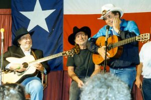 Photograph of Bobby Bare singing with Willie Nelson and bluegrass great Mac Wiseman. All three are now members of the Country Music Hall of Fame.