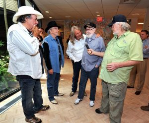 A photograph of Hank Cochran sharing a laugh at a BMI reception honoring him for 50 years of his great music. Fellow songwriter Red Lane is holding the mic with Merle Haggard and Bobby Bare looking on.