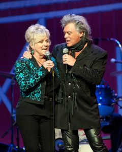 Photograph of Connie Smith and Marty Stuart on stage performing together at Marty's Stuart's late night jam in 2014 taking place at the Ryman Auditorium in Nashville, TN