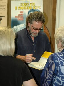Photograph of David Frizzell autographing his book for one of the many fans at the Willie Nelson General store in Nashville.