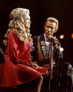 Color photograph of Dolly Parton alongside Porter Wagoner on the set of the Porter Wagoner TV show. during the 1960s.