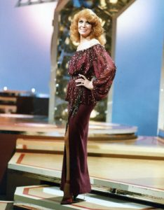 A photograph of Dottie West on stage during a TV show appearance in the 1970s.