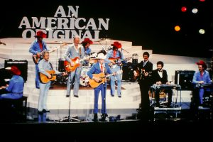 Photograph of Ernest Tubb and the Texas Troubadours performing on stage during a TV show titled an American Original..