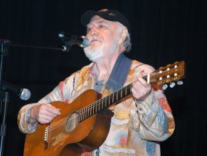 A photograph of Hank Cochran picking his guitar and singing.