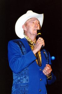Photograph ofJack Greene performing at a show wearing a fancy blue suit and white cowboy hat.