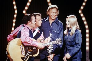 A photograph of Jack Greene, Jeannie Seely talking to the Wilburn Brothers on the set of the Wilburn Brothers TV Show.