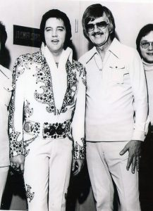 Photograph of J.D. Sumner with his buddy Elvis Presley in a white and gold stage costume following a concert.