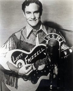 Photograph of Lefty Frizzell and his famous 1949 Gibson SJ-200 guitar learning a Nudie suit in front of a WSM microphone.
