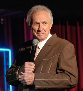 Image of Mel Tillis on stage holding a microphone wearing a brown western suit.