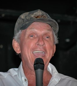 Image of Mel Tillis wearing a camo cap while performing and cracking jokes at a benefit show at the Nashville Palace.