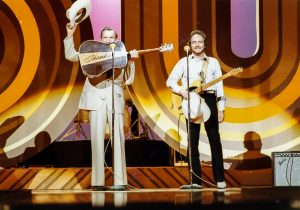 Photograph of Ernest Tubb and Merle Haggard perform together during the taping of a national TV show Pop Goes the Country.
