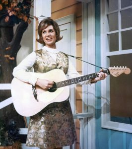 Photo of Norma Jean with her guitar singing on the set of the Porter Wagoner TV show in the 1960s.