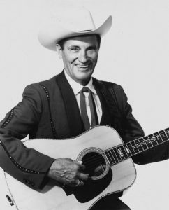 Photograph of Ernest Tubb with guitar and cowboy hat.