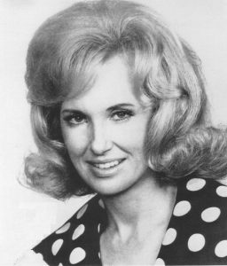 A black and white photograph of Tammy Wynette in a black dress with white polka dots in the 1970s.