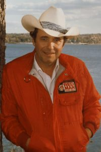 Photograph of Bobby Bare wearing cowboy hat by lake.