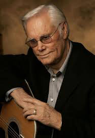 Photograph of George Jones in suit with his guitar.