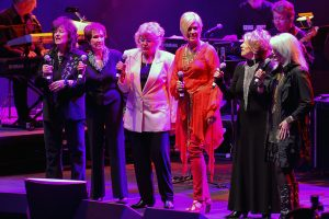 Photograph of Jan Howard singing at the George Jones Tribute Show along with other female stars including Jeannie Seely, Emmy Lou Harris, Leona Williams and others.