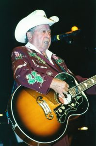 Photograph of Grand Ole Opry legend Little Jimmy Dickens singing and playing guitar wearing a Maroon Nudie suit and wearing a white cowboy hat.