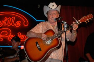 Photo of Grand Ole Opry star Little Jimmy Dickens playing his guitar at the Nashville Palace wearing a white cowboy hat.