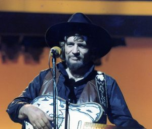 A photograph of Waylon Jennings on stage with his famous Fender Telecaster guitar.