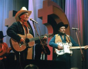 A photograph of Waylon Jennings and Willie Nelson performing together during one of their many TV appearances.